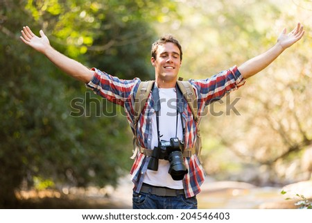 young photographer arms open in mountain valley - stock photo