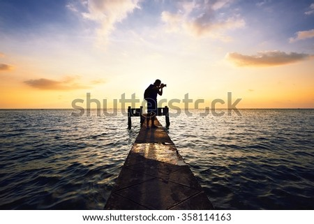 Young photographer is taking photos at the sunset. - stock photo