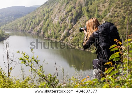 Young photographer shooting nature. - stock photo