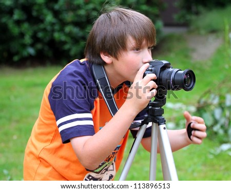 Young photographer takes pictures on the nature . - stock photo