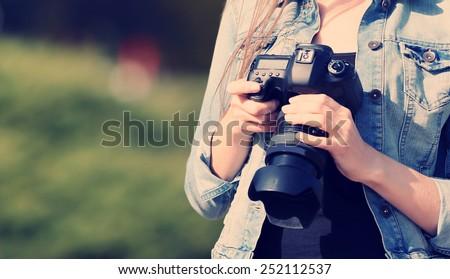 Young photographer taking photos outdoors - stock photo