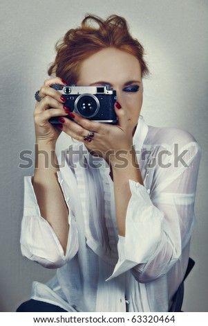 young photographer woman in white shirt and fashion make-up taking picture with vintage Soviet film camera with cross-process effect - stock photo