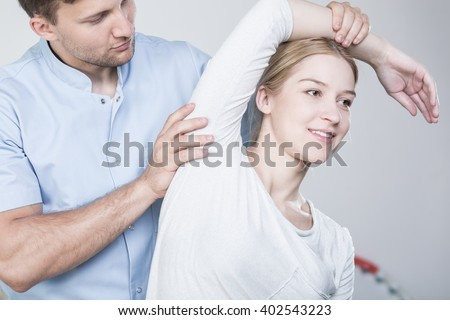 Young physiotherapist stretching woman's arm during rehabilitation - stock photo