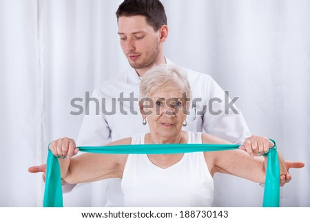 Young physiotheraqpist assisting elderly woman in exercising - stock photo