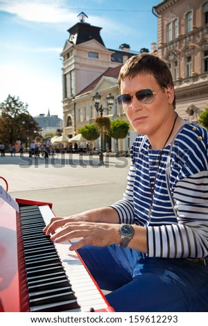 Young pianist play on his piano with bright emotions, Novi Sad, Serbia. - stock photo