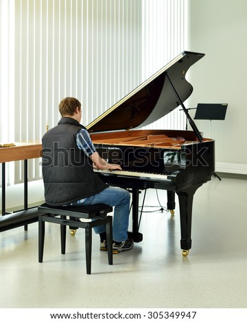 Young pianist plays on black grand piano - stock photo
