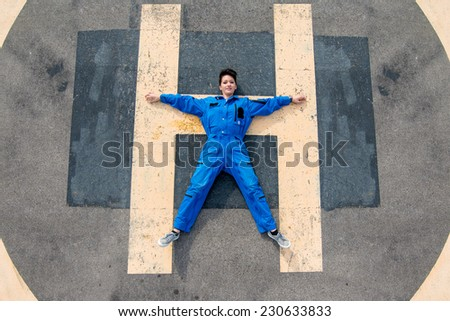 Young Pilot laying down on helicopter runway - stock photo