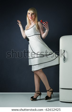 Young pin-up sexy girl with white mini dress jammed fridge door - stock photo