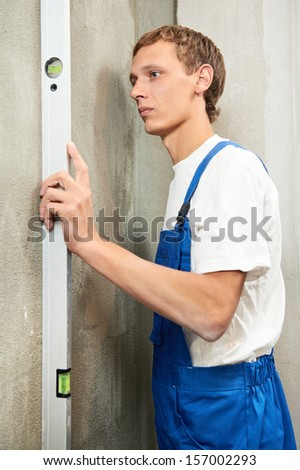 Young plasterer worker checking wall with level before wallboard installation - stock photo