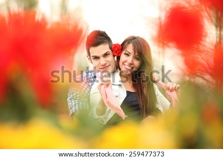 young playful couple in love sitting in park - stock photo