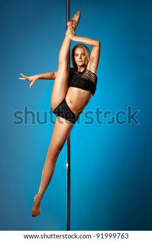 Young pole dance woman on blue background. - stock photo