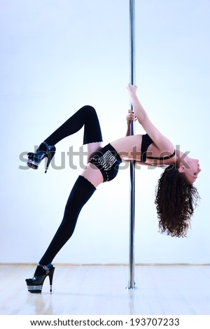 Young pole dance woman on wall background. - stock photo