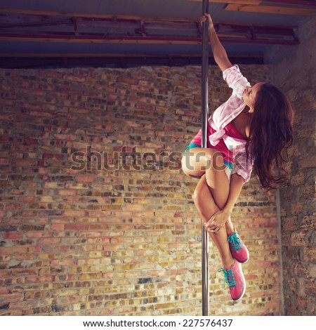 Young pole dancer woman wearing colorful sports wear trains on grunge interior with brick walls, right side align, square composition - stock photo
