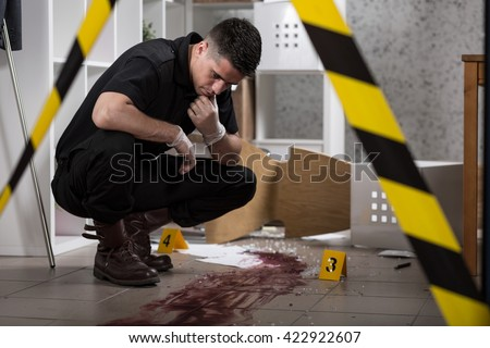 Young policeman collecting evidence standing behhind yellow crime scene tape - stock photo