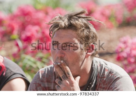 Young poor man smoking while sitting outdoors during the daytime. - stock photo