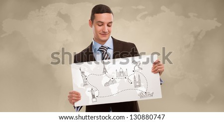 Young positive business man holding banner with world map and famous symbols. Business travel concept - stock photo