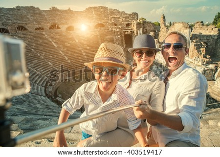 Young positive famly take a vacation photo on the Side ampitheatre view - stock photo