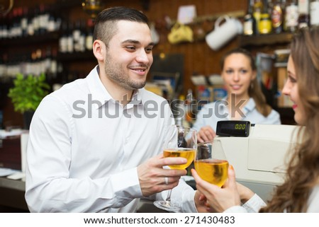 Young positive restaurant visitors waiting for table and drinking wine at bar - stock photo