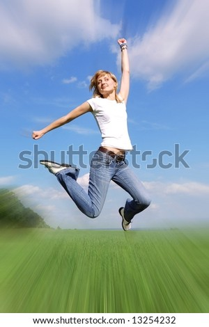 Young positive woman jumping at the field - stock photo