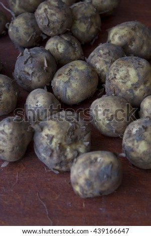 Young potatoes on wooden table - stock photo