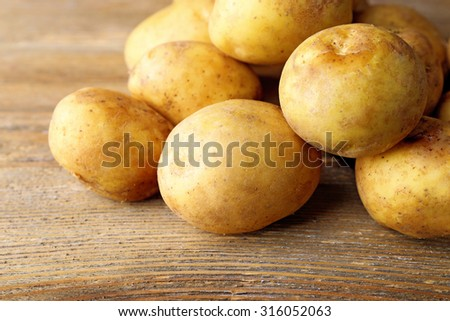 Young potatoes on wooden table close up - stock photo