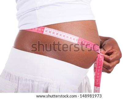 Young pregnant black woman measuring her belly, isolated on white background - African people - stock photo