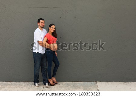 Young pregnant couple in a loving pose. - stock photo