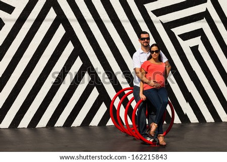 Young pregnant couple in a loving pose in a urban setting. - stock photo