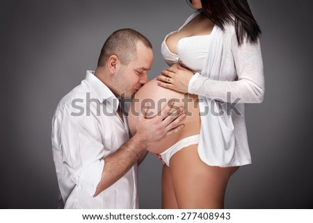 young pregnant couple isolated over gray background - stock photo