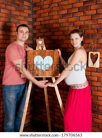 young pregnant couple. Studio shoot - stock photo