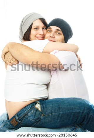 young pregnant woman and her excited husband embracing - stock photo