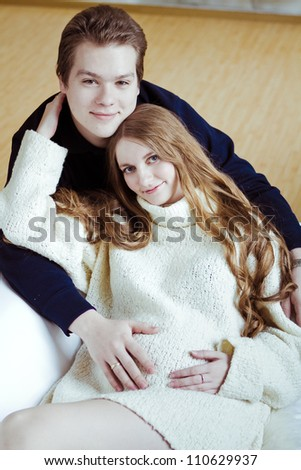 young pregnant woman and man sitting on sofa - stock photo