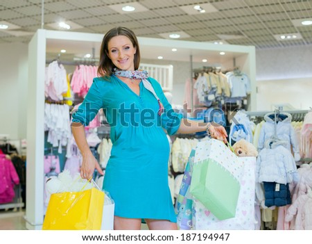 Young pregnant woman choosing newborn clothes at baby shop store - stock photo