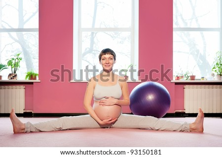 Young pregnant woman doing pregnancy yoga - stock photo