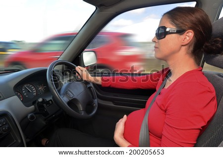 Young pregnant woman drive a car during pregnancy. Concept photo of pregnancy, pregnant woman lifestyle , transportation and health care. - stock photo