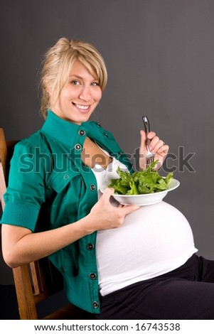 young pregnant woman eating healthy fresh green salad - stock photo