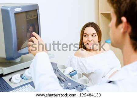 Young pregnant woman examined by doctor at ultrasound check - stock photo