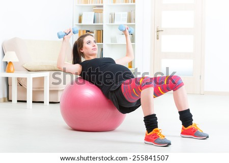 Young pregnant woman exercising with dumbbells and gym ball at home - stock photo
