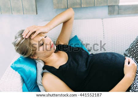Young pregnant woman having a headache and she is lying on the sofa holding her belly and forehead  - stock photo