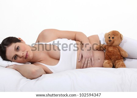young pregnant woman in bed - stock photo