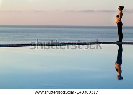 Young pregnant woman is standing by the pool - stock photo