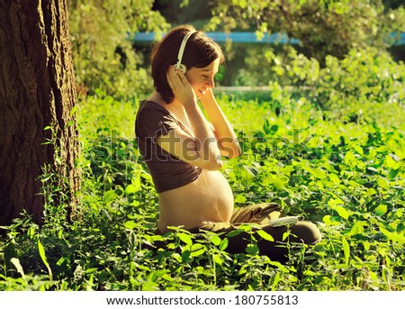 Young pregnant woman listening to a music at park. - stock photo