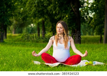 young pregnant  woman meditating in nature, practice yoga. Care of health and pregnancy - stock photo