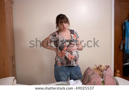 Young pregnant woman packing to go to hospital - stock photo