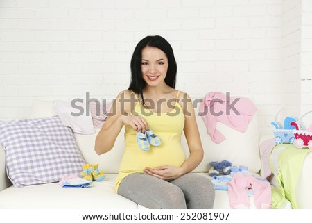 Young pregnant woman relaxing on sofa, close-up - stock photo