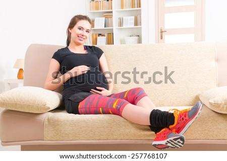 Young pregnant woman resting after doing finess at home - stock photo