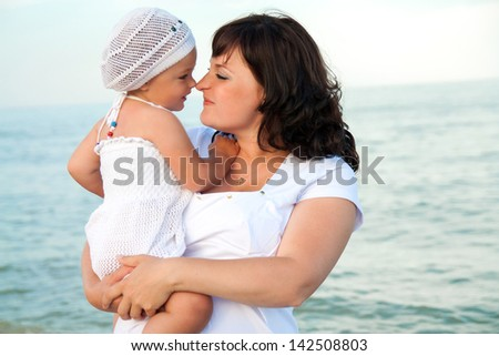 Young pregnant woman with her daughter on the beach. - stock photo
