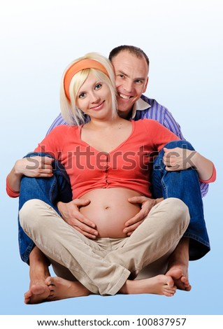 Young pregnant woman with husband - stock photo
