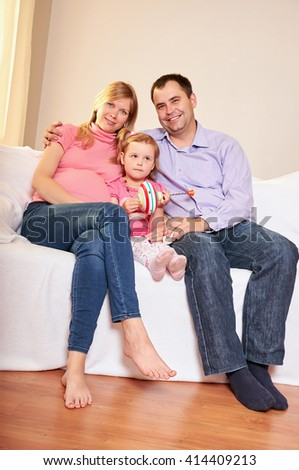 Young pregnant woman, with husband and little daughter  - stock photo