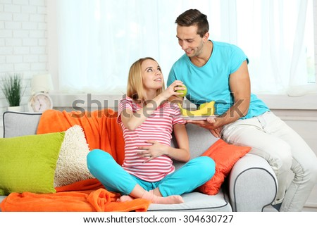 Young pregnant woman with husband on sofa in room - stock photo